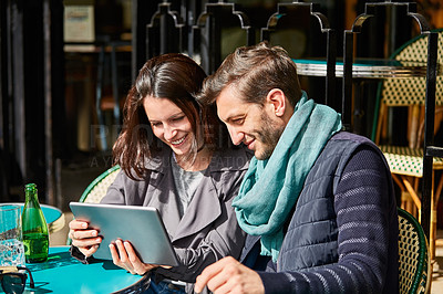 Buy stock photo Shot of a smiling couple sitting together at a table at a sidewalk cafe using a digital tablet