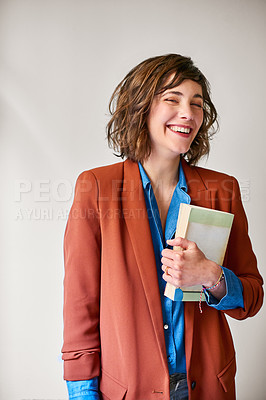 Buy stock photo Shot of a laughing young woman holding a book while standing against a gray background