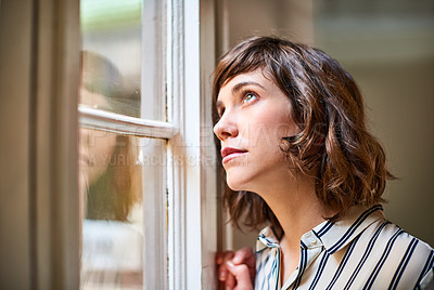 Buy stock photo Shot of a young woman looking up through a window at home