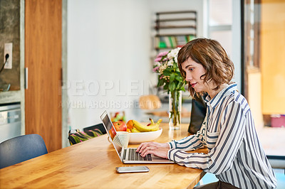 Buy stock photo Shot of a young woman sitting at her kitchen table working on a laptop