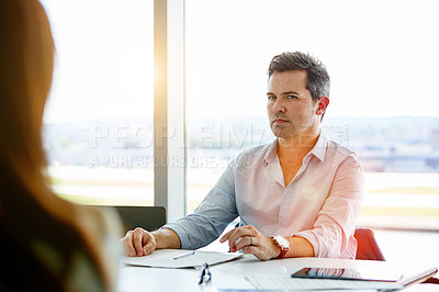 Buy stock photo Shot of two coworkers talking together while sitting in an office