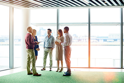 Buy stock photo Shot of a group of colleagues talking together while standing in an office hallway