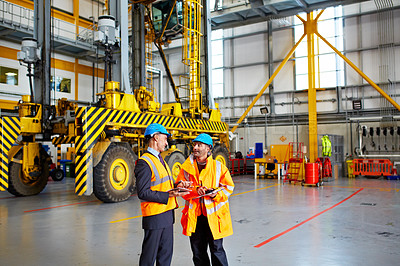 Buy stock photo Shot of two warehouse workers talking together inside of a large warehouse