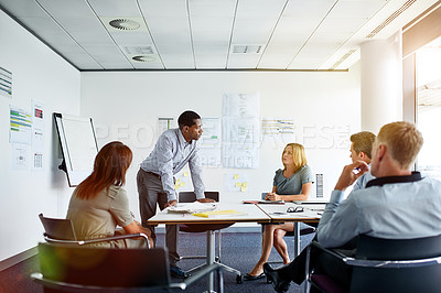 Buy stock photo Shot of a man giving a presentation to colleagues in an office boardroom