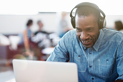Buy stock photo Shot of a man wearing headphones and working on a laptop in an office with colleagues in the background