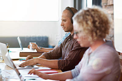 Buy stock photo Shot of people sitting in a row at a table in an office working on laptops