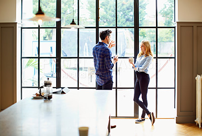 Buy stock photo Shot of a young couple drinking coffee together by a window in their kitchen