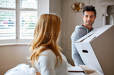 Buy stock photo Shot of a happy young couple carrying boxes in their new house