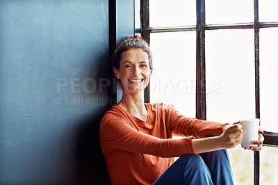 Buy stock photo Portrait of an attractive mature woman sitting on a window sill at home drinking a cup of coffee
