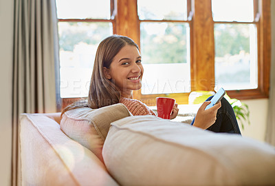 Buy stock photo Portrait of a young woman sitting on her living room sofa drinking a coffee and using a cellphone