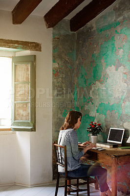 Buy stock photo Shot of a young woman sitting at a desk in her room using a computer