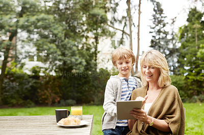 Buy stock photo Shot of a grandmother and her grandson using a digital tablet while eating lunch at a table in her yard