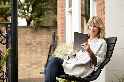Buy stock photo Shot of a mature woman sitting on a bench on her front porch using a digital tablet