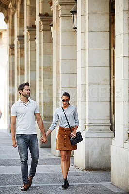 Buy stock photo Shot of an affectionate young couple walking together in the city