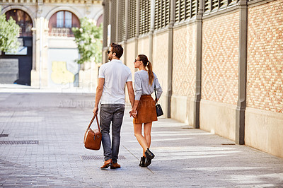 Buy stock photo Rearview shot of an affectionate young couple walking hand in hand together in the city