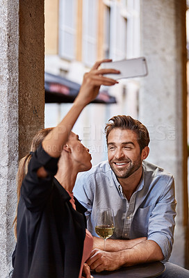 Buy stock photo Shot of a young couple sitting at a sidewalk table taking a selfie while drinking wine