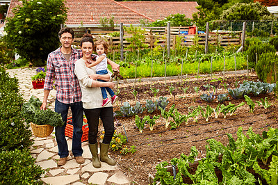 Buy stock photo Portrait of a smiling couple and their little daughter standing in their organic garden