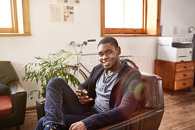 Buy stock photo Portrait of a smiling young man using a cellphone while sitting in an office