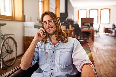 Buy stock photo Shot of a young designer talking on his phone while sitting in an office