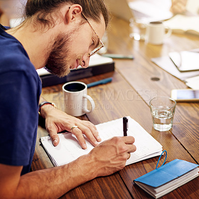 Buy stock photo Shot of a smiling young man writing in notebook while sitting at a table in an office