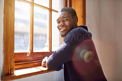 Buy stock photo Portrait of a smiling young man leaning on a window sill