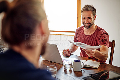 Buy stock photo Shot of man handing documents to a coworker while sitting at a table in an office