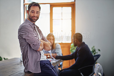 Buy stock photo Portrait of a smiling man standing in an office with colleagues working in the background
