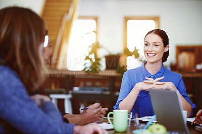 Buy stock photo Shot of a smiling young woman talking with colleagues while sitting at a table in office