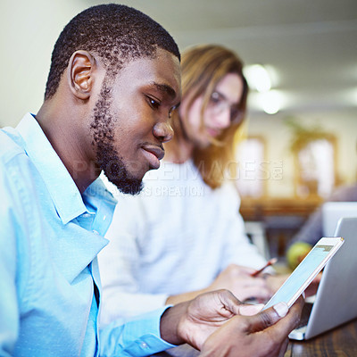 Buy stock photo Shot of a smiling young man sitting in an office using a digital tablet with a colleague in the background