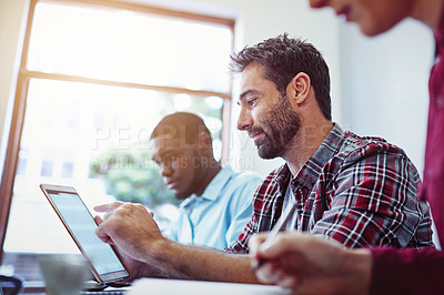 Buy stock photo Shot of man sitting at a table using a digital tablet with colleagues working around him