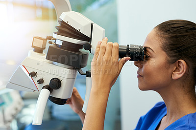 Buy stock photo Shot of a young pathologist looking at samples under a microscope