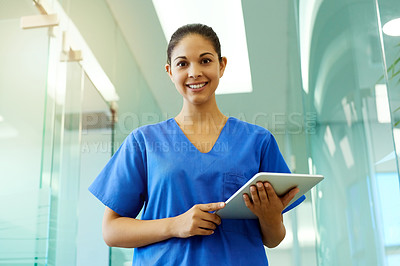 Buy stock photo Portrait of a young nurse using a tablet while standing inside a clinic