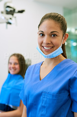 Buy stock photo Portrait of a young female dentist standing in her office with a patient in the background