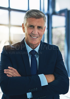 Buy stock photo Portrait of a confident businessman posing with his arms crossed in the office