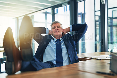 Buy stock photo Shot of a contented businessman relaxing with his feet on his desk