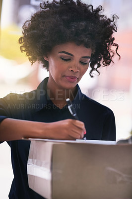 Buy stock photo Shot of a businesswoman signing for a package delivered by a courier in her office