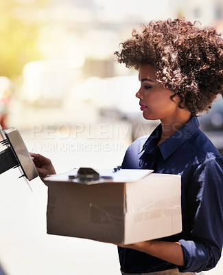 Buy stock photo Shot of a focused young delivery woman out on a delivery