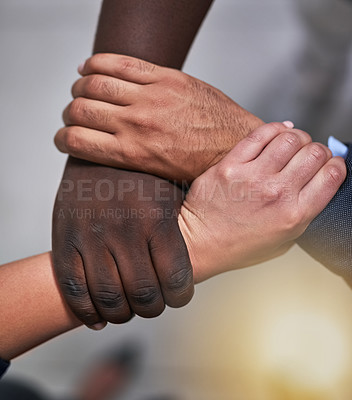 Buy stock photo High angle shot of three unidentifiable coworkers holding each other's hands in  the office
