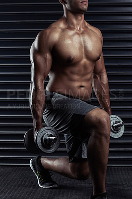 Buy stock photo Cropped shot of an unrecognizable young man working out with dumbbells