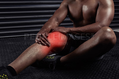 Buy stock photo Shot of an unrecognizable man sitting down with a knee injury during a workout