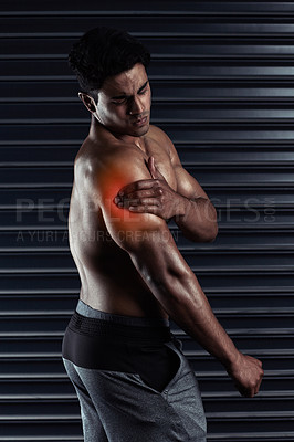 Buy stock photo Cropped shot of an athletic young man holding his shoulder in pain during a workout