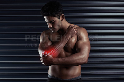 Buy stock photo Cropped shot of an athletic young man holding his elbow in pain during a workout