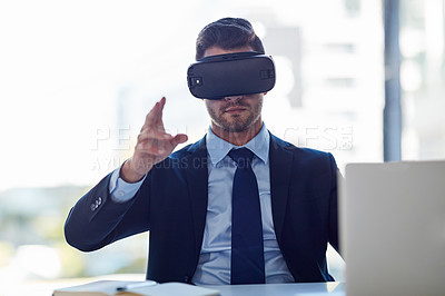 Buy stock photo Shot of a businessman wearing a VR headset while working in his office