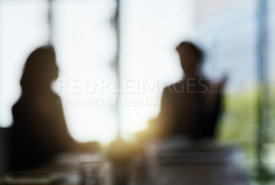 Buy stock photo Defocussed shot of two silhouetted businesspeople having a meeting in the boardroom