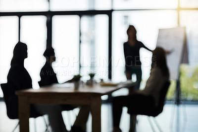 Buy stock photo Defocussed shot of a team of businesspeople attending a meeting in the boardroom