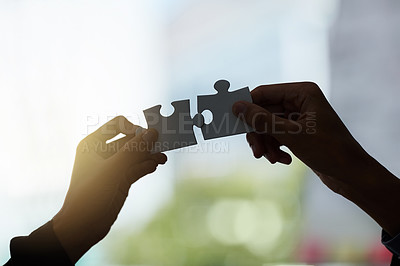 Buy stock photo Cropped shot of two silhouetted hands holding puzzle pieces against a window