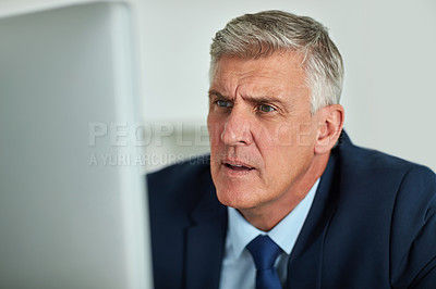 Buy stock photo Shot of a mature businessman looking frustrated while working on his computer in the office