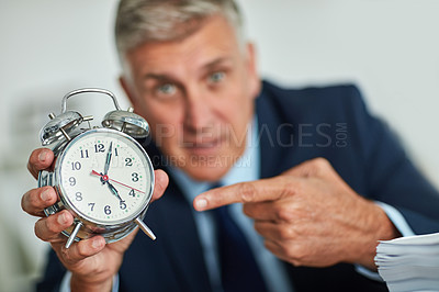 Buy stock photo Portrait of a mature businessman gesturing toward a clock in frustration