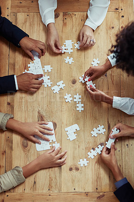 Buy stock photo High angle shot of a group of unrecognisable businesspeople building a puzzle together