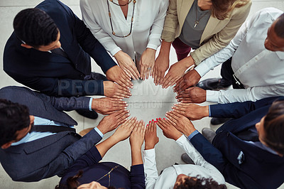 Buy stock photo High angle shot of a group of businesspeople joining their hands together in unity